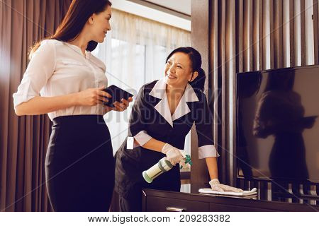 Friendly conversation. Attractive hotel guest standing in semi position and holding tablet in both hands while looking at room cleaner