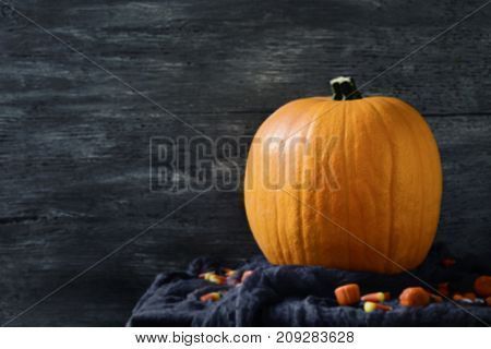 closeup of a pumpkin and some halloween candies on a rustic surface against a gray wooden background with a blank space on the left