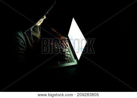Hacker with laptop wearing hoodie- top view