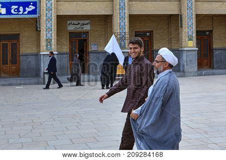 Fars Province Shiraz Iran - 19 april 2017: Shah Cheragh Shrine A Muslim clergyman passes through the courtyard of the mosque together with his young subordinate.