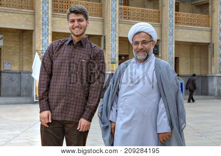 Fars Province Shiraz Iran - 19 april 2017: Shah Cheragh Shrine An elderly Muslim cleric in a white turban and his young companion posing for a photographer in the courtyard of the mosque.