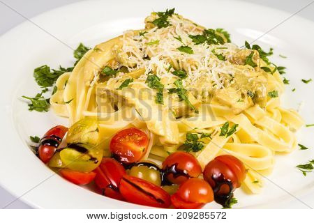 Fresh handmade tagliatelle pasta with forest mushrooms parsley and cherry tomatoes salad on white