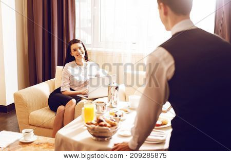 Come in. Charming female keeping smile on her face and working with laptop while sitting in cozy arm-chair