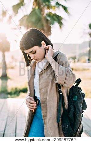 Very petite trendy hipster millennial woman with short haircut poses to photographer on beach promenade in sunset light fixes her hair looks down fashionable and impressive