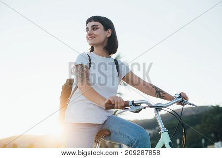 Beautiful young attractive woman sits in seat of her cruiser commuter city bicycle looks around for safety and traffic amazing sunlight she smiles and laughs full of hope
