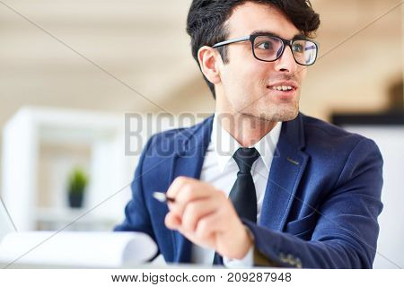 Young employee in suit having talk with co-worker or client