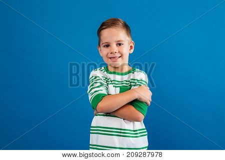 Portrait of a smiling young kid standing with arms folded isolated over blue background