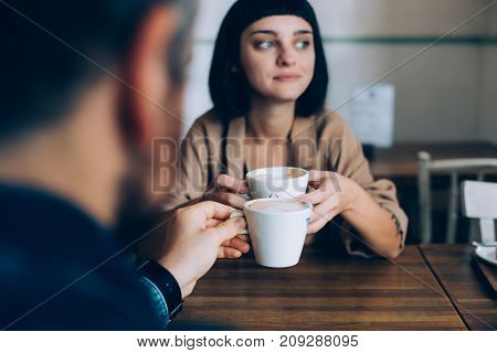 Woman and man partners of boyfriend and girlfriend are on romantic date getaway in cute adorable cafe they drink coffee with milk beautiful girl looks out into window