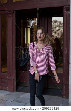 Beautiful blonde model in red triped shirt and with leather shoulder bag leaves office building on way to meeting looks back at camera hair blows in wind wears hipster glasses