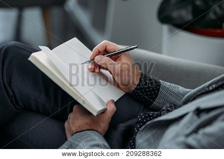 close-up partial view of businessman writing in notebook