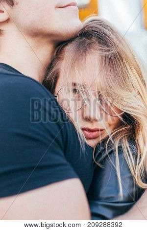 Portrait closeup of attractive beautiful girl or young woman hugging her boyfriend messy hair and casual outfit cute love story of teenager during summer break