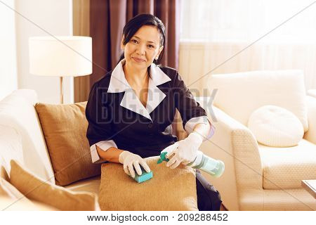 Furniture cleaner. Charming foreign worker keeping smile on her face and sitting on the sofa while cleaning pillow