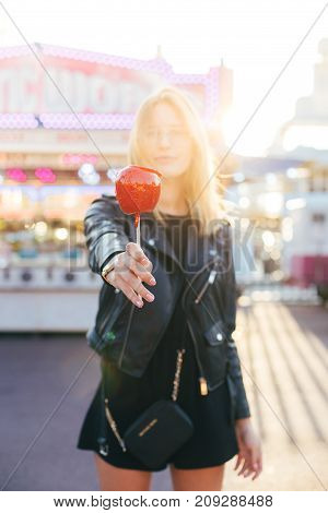 Cute and pretty blonde happy woman in cool looking leather jacket poses for camera shows and draws out hand holds toffee caramel sugar candy apple at carnival fair