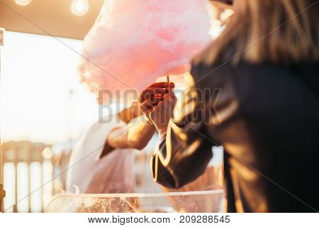 Close up soft focus shot of woman paying buying recieving big pink cloud of sugar cotton candy from street vendor at festival or carnival