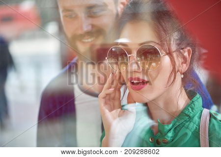 Young attractive woman looking excited while shopping with her boyfriend examining jewelry on display at the local boutique.