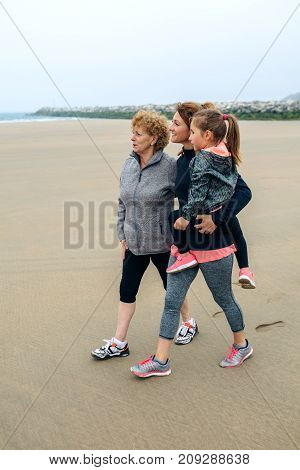 Three generations female looking at sea on the beach in autumn