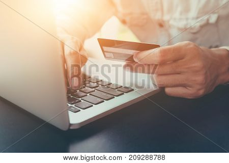 Online Payment,man's Hands Holding Caredit Card And Using Laptop Computer For Online Shopping.