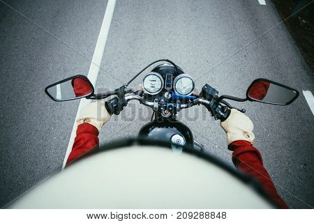 View of experienced motorcycle driver riding his vehicle through highway or mountain road turning on corners wears leather gloves and retro vintage helmet