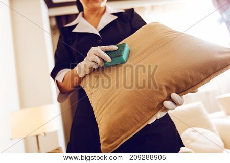 Anti-dust effect. Competent hotel cleaner holding mop in right hand while using it in her work