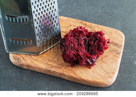 Grated Boiled Beetroot On An Olive Wood Cutting Board.