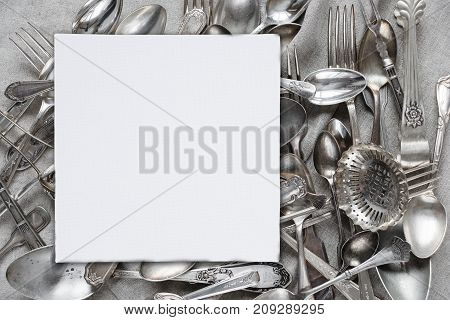 Creative layout with various silverware and blank white paper card are on a background of gray linen fabric