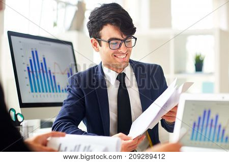 Young financier reading documents and discussing financial data with colleague