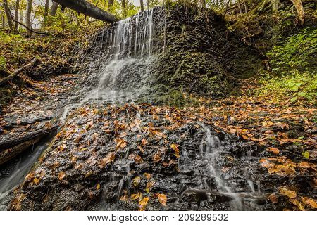 Waterfalls flow smoothly over rocks surrounded by lush fall foliage in Delaware Water Gap, PA