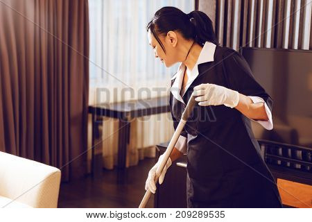 While working. Attractive woman bowing head while swabbing floor and being in special uniform