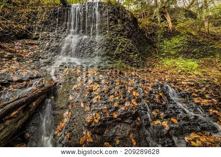 Waterfalls flow smoothly over rocks surrounded by fall foliage in Deleware Water Gap section of Pocono Mountains, PA