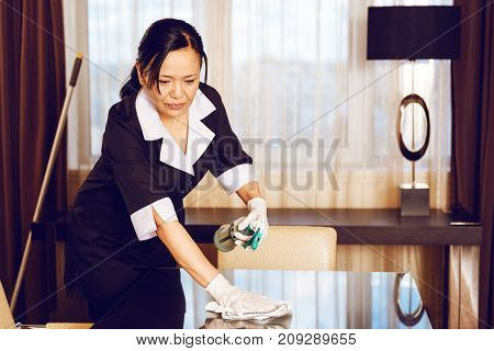 Glass polishing. Serious hotel worker dispersing cleaning liquid on glass table while polishing it and looking downwards