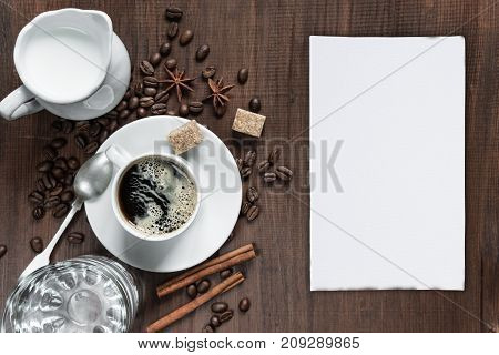 Cup of coffee cream in a milk jug glass of water white blank paper card and various spices on the wooden table with copy-space top view