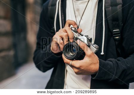 Closeup of man in hipster outfit black hoodie cardigan and white tshirt holding vintage analog film camera zooming and focusing