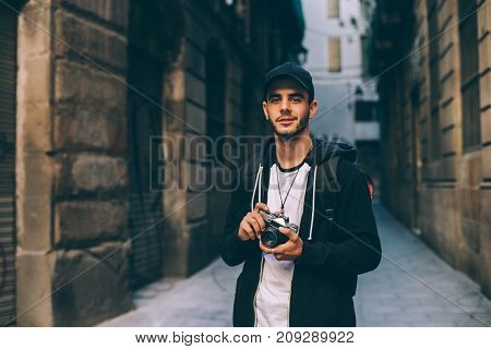 Attractive young man student or freelance photographer smiles and laughs into camera explores historic center of city or village urban adventurer nomad travels the world
