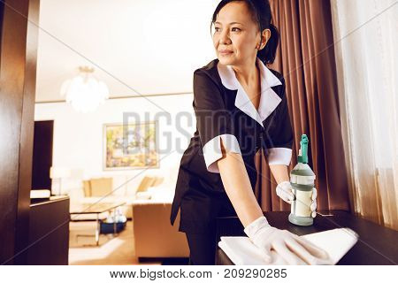 Do not distract me. Serious hotel cleaner polishing table while looking aside and being deep in thoughts