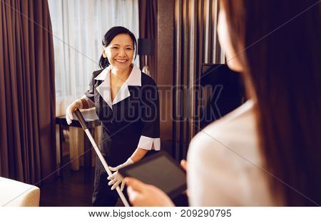 It is me. International brunette woman wearing special uniform and smiling while standing opposite her guest