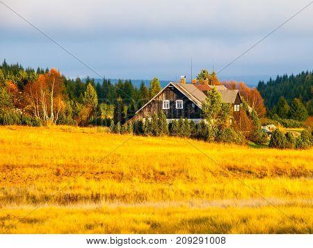 Wooden hut in Jizerka village. Sunny autumn day. Jizera Mountains, Czech Republic.