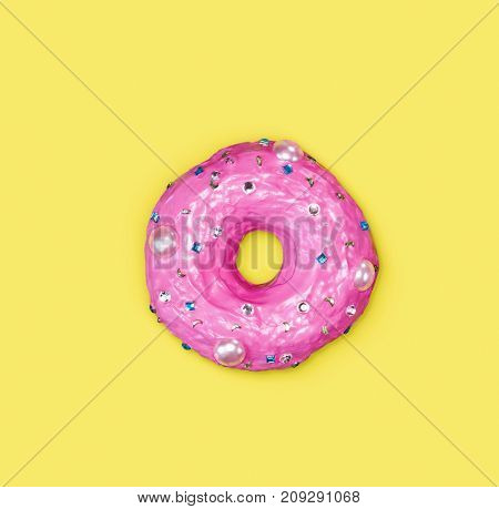 A photo of a donut, decorated with caramel, which looks like rhinestones, on yellow background.