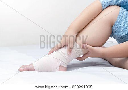 Child Touching Ankle With Elastic Bandage, Broken Leg
