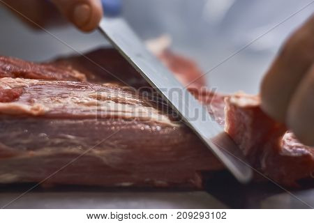 Butcher Cleaning The Meat From Impurities