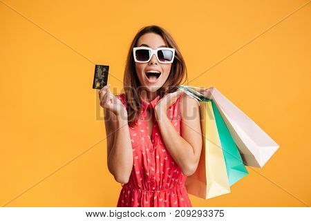 Close-up of happy exited brunette woman in sunglasses holding credit card and colorful shopping bags, looking at camera, isolated on yellow background