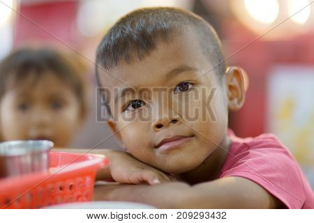 SHIRA THANI, THAILAND, SEPTEMBER 28, 2016 : A shy little boy is posing in the night market of Shira Thani, Isaan ,Thailand