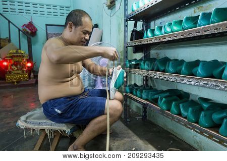 BANGKOK, THAILAND, SEPTEMBER 23, 2016 : A man is working in a local little shoes factory in the Talat Phlu district in Bangkok, Thailand
