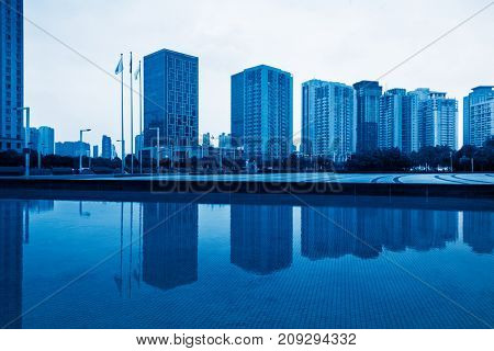 modern highrises reflected on park pond,blue toned,tianjin,china.
