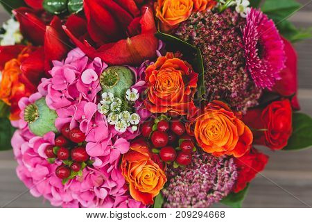 Rustic wedding bouquet with orange, crimson and bordeaux roses, poppy and other flowers and greens on wooden background. Close-up.. Copy space
