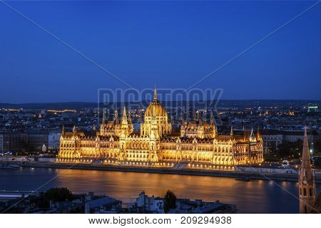 Night view of Hungarian Parliament building illuminated next to Danube river