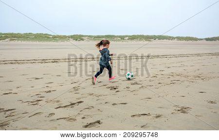 Little girl playing soccer on the beach in autumn
