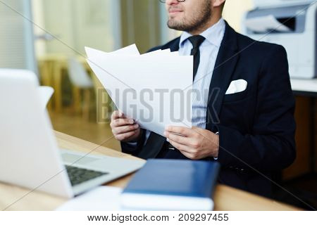 Young economist with financial papers sitting by workplace