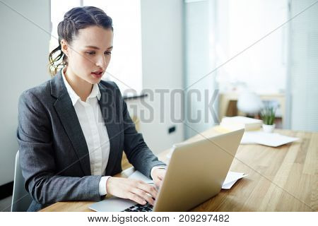 Young office worker sitting in front of laptop and entering information