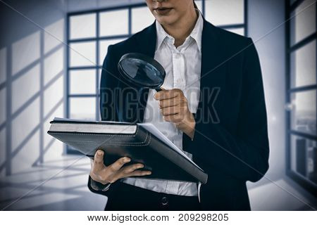 Businesswoman looking at document through magnifying glass against room with large windows showing city