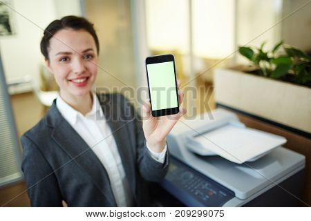 Young manager showing her smartphone with hot offer or promo